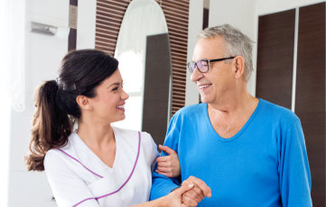 Young beautiful nurse helps to a senior man at bathroom nursing home