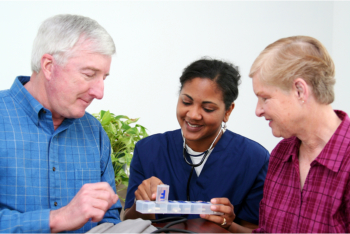 elderly couple and their caregiver holding a medicine kit